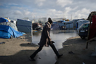 A man is seen jumping a puddle in the migrants camp. Many areas have been flooded by the recents rains. Calais, France. FEDERICO SCOPPA/CAPTA