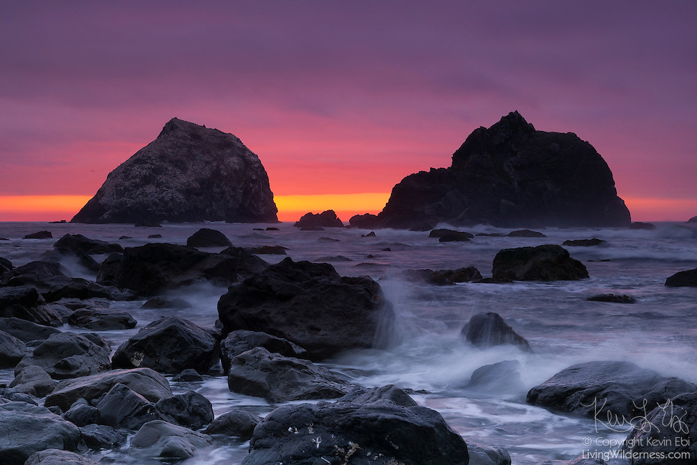 A colorful fall sunset lights up the sky above two large sea stacks on the North California Coast near Klamath.