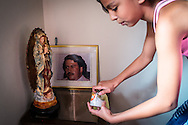 "2015/11/23 - Medellín, Colombia: Maria Miranda, 17,  lights a candle in the  altar in her father's house in honor of Pablo Escobar, Colombia's most famous drug lord. Habitants of the Escobar neighbour are forever grateful to Pablo Escobar. Originally called ""Medellin Sin Tugurios,"" or Medellin Without Shanty Towns, Barrio Pablo Escobar is located high up on the eastern slope of Medellin, where Pablo Escobar built 413 houses, which he gave to poor people that used to live in a mountain of garbage in the Moravia neighbourhood. (Eduardo Leal)"