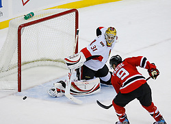 Jan 4, 2008; Newark, NJ, USA; New Jersey Devils left wing Zach Parise (9) tips a shot wide of Ottawa Senators goalie Alex Auld (31) during overtime at the Prudential Center. The Devils defeated the Senators 4-3 in overtime.