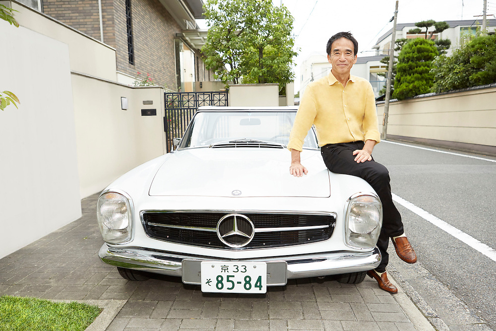 Lifestyle image of middle age guy sitting on white vintage Mercedes Benz car