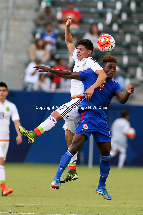 Mexico midfielder Arturo Alfonso González González #7, left, and Haiti midfielder Fernander Demas #6 fight for the head ball in the first half of a CONCACAF men's Olympic qualifying soccer match in Carson, Calif., Sunday, Oct. 4, 2015. (AP Photo/Ringo H.W. Chiu)