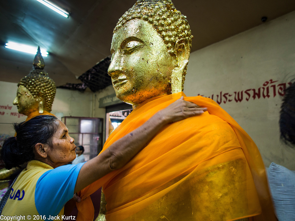 14 JANUARY 2016 - CHACHOENGSAO, CHACHOENGSAO, THAILAND: A woman wraps an orange cloth around a statue of the Buddha to make merit at Wat Sothon. Wat Sothon, in Chachoengsao, is one of the largest Buddhist temples in Thailand. Thousands of people come to the temple every day to pray for good luck, they make merit by donating cooked eggs and cash to the temple. The temple dates from the Ayutthaya period (circa 18th century CE).          PHOTO BY JACK KURTZ
