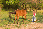 A young girl talks to a horse in a pasture on a sunny summer afternoon.