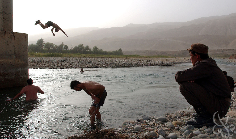 BANGHI RIVER, AFGHANISTAN - SEPTEMBER 2: An Afghan army soldier (r) stands guard and watches as U.S. Army Special Forces soldiers take a break from their patrolling and reconnaissance of Northern Afghanistan by taking a dip September 2, 2002 in the Banghi river in Afghanistan.