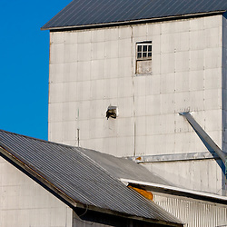 The details of a small grain elevator complex reflect the late afternoon sun in the small town of Big Rock, IL.