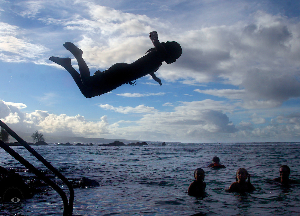 A Hawaiian boy jumps high off of a hand rail into the water as he and others enjoy a swim off of Hilo Bay about Carlsmith Beach Park on the Big Island.
