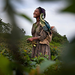 Fifteen-year-old Destaye stands in a field with her son near Bahir Dar, Ethiopia on Aug. 9, 2012. Destaye and her husband Addisu, 27, divide their time between working in the fields and taking care of their 6-month-old baby. Like many other young couples, they tend to the domestic, economic and personal demands of being young parents. At the time of their marriage, when Destaye was age 11, she was still in school and her husband expressed interest in letting her continue her education. Since the birth of their son, however, she has had to confine her life exclusively to being a wife and mother.