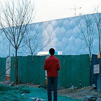 BEIJING, MARCH :7 : a man looks at the aqua centre.