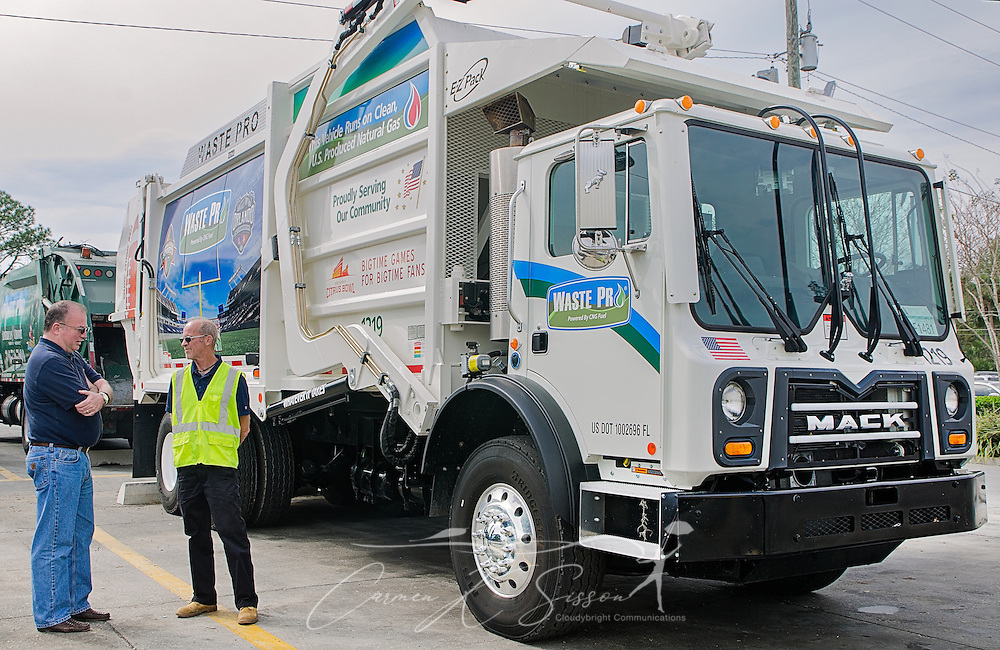 """Tim Dolan, Waste Pro Regional Vice President for Central Florida, talks with operations specialist Terry Grady at Waste Pro, March 18, 2016, in Sanford, Florida. Waste Pro offers waste and recycling services to more than two million residential customers and more than 40,000 businesses in Alabama, Florida, Georgia, South and North Carolina, Louisiana, Mississippi, and Tennessee. The company has committed to """"going green"""" by implementing a number of green initiatives, including using CNG (Clean Natural Gas) in its trucks, recycling more waste instead of sending it to landfills, and powering its regional headquarters throuh solar energy. (Photo by Carmen K. Sisson/Cloudybright)"""