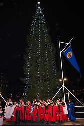 Trafalgar Square, London, December 4th 2014. The Lord Mayor of Westminster Councillor Audrey Lewis and the Governing Mayor of Oslo, Stian Berger Rosland attend the switching on of the lights decorating the Christmas tree in Trafalgar Square. The tree is an annual gift to the people of London from the people of Oslo in thanks for British support during World War II. PICTURED: St Martin-In-The Fields choir sings Silent Night with the tree illuminated in the background.