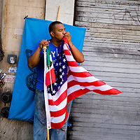 An immigrant kisses the American flag as he watches immigrant rights supporters march in Los Angeles as part of May Day celebration.