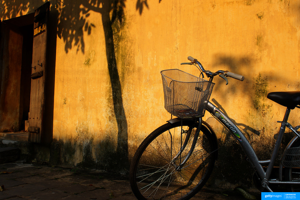 A bicycle parked against a bright yellow wall in Hoi An, Vietnam. Hoi An is an ancient town and an exceptionally well-preserved example of a South-East Asian trading port dating from the 15th century. Hoi An is now a major tourist attraction because of its history. Hoi An, Vietnam. 5th March 2012. Photo Tim Clayton