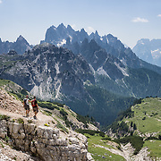 """Hikers admire sharp peaks of the Cadini Group in the Sesto Dolomites, Veneto region, Italy, Europe. In the Cadini di Misurina, Cima Grande rises to 2999 meters (9839 feet), between Cima Piccola and Cima Ovest. The Cadini Group is in the municipality of Auronzo, in the Sesto Dolomites (Dolomiti di Sesto, or Sexten/Sextner/Sextener Dolomiten) which lie north of the Fiume Ansiei valley. From the Rifugio Auronzo toll road, hike for spectacular views around Tre Cime di Lavaredo (Italian for """"Three Peaks of Lavaredo,"""" called Drei Zinnen or """"Three Merlons"""" in German). The Dolomites are part of the Southern Limestone Alps. UNESCO honored the Dolomites as a natural World Heritage Site in 2009."""