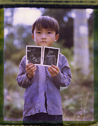 Polaroid 79 portrait of a young boy showing off his Polaroids, Ha Giang Province, Northern Vietnam, Southeast Asia