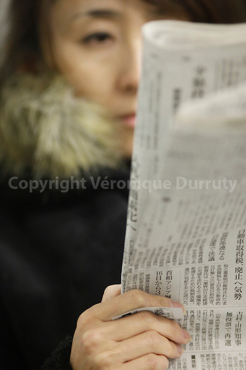 Woman reading a newspaper,Tokyo metro, Japan / Femme lisant le journal Dans le métro de Tokyo, Japon