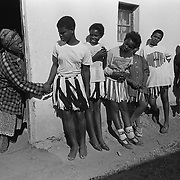 A woman reaches for a young girl waiting to be examined for virginity by a group of mothers in Magqabasini village, near Flagstaff in the former Transkei July 20, 1999, as others wait their turn.  This tradition has been revived to combat child abuse and high rates of teenage pregnancies and the spread of HIV. (Greg Marinovich)