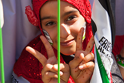 London, August 9th 2014. A girl gives a double 'V' for Victory sign after marching with tens of thousands of other Palestinians and their supporters, from the BBC headquarters to a Rally in Hyde Park.