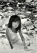 A young girl sifts through some of the refuse in a giant garbage dump in Guatemala City. About 700 people live in the dump itself, and another 1200 live in a shantytown just outside the walls. They spend most of their days going through the garbage for anything they can eat or resell.&amp;#xD;&amp;#xD;Guatemala City, 1991.<br />