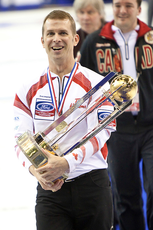 Canadian skip Jeff Stoughton carries the world championship trophy after their victory over Scotland in the gold medal game at the Brandt Centre in Regina, Saskatchewan, April 10, 2011.<br /> AFP PHOTO/Geoff Robins