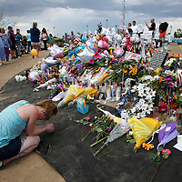 A woman kneels at the memorial to the movie theater shooting victims in Aurora July 25, 2012. First responders got their first look at the growing memorial today.   REUTERS/Rick Wilking (UNITED STATES)