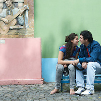 A couple shares a tender moment in the colorful barrio of La Boca in Buenos Aires, Argentina