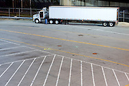 The driver of this plain white tractor trailer rig checks the brake and light connections to the trailer before hitting the road.