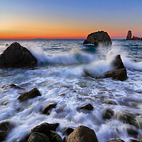 A sunset view of Cala del Gesso, a small bay on the northern end of Isola del Giglio in the Tuscan Archipelago, italy, with some nice breaking waves on the rocky shore.