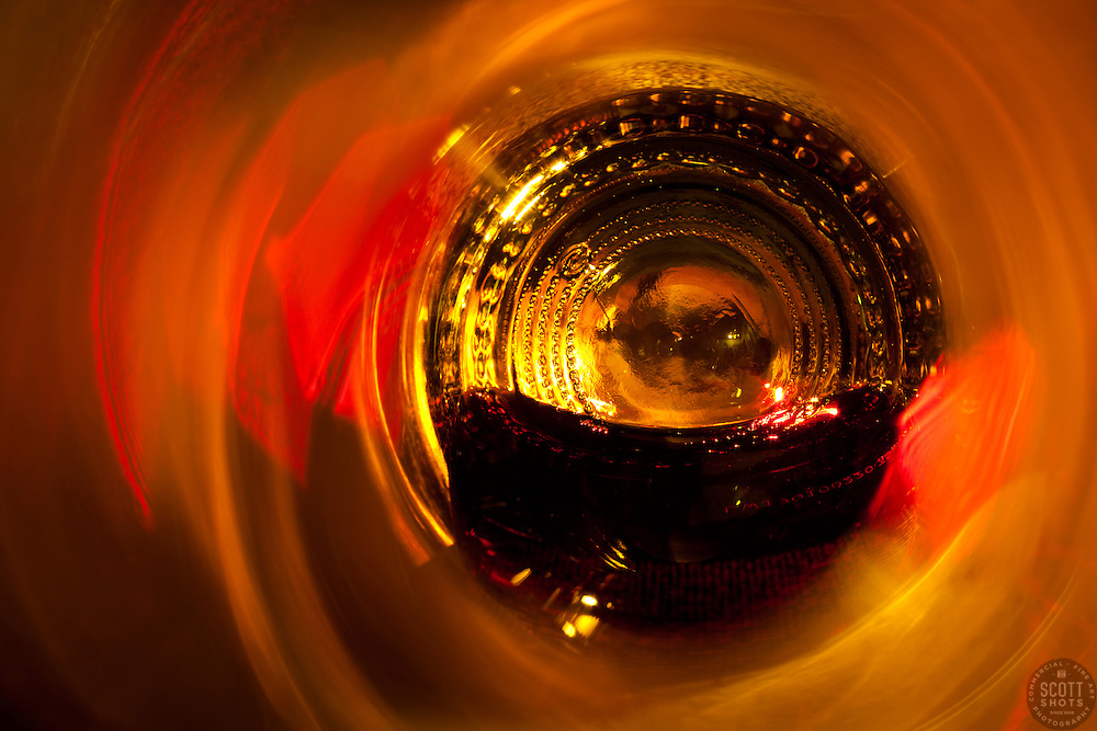 """""""Beauty at the Bottom: Red Wine 4"""" - This is a photograph of a red wine bottle bottle, shot right down inside the mouth of the bottle. A fire behind the bottle provides the main lights source."""
