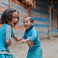 A sister and her brother laugh while at play in the village of Giabong in the Ropa Valley, Himachal Pradesh, India