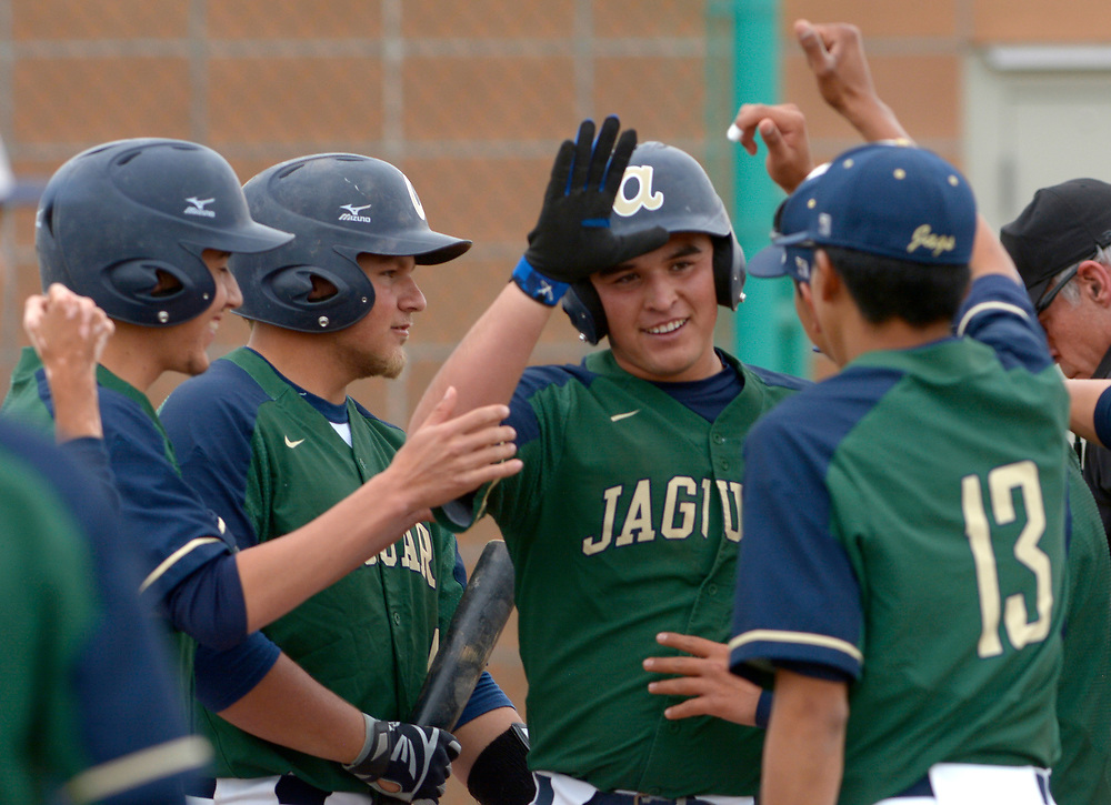 gbs041117h/SPORTS --Artisco Heritage's Steven Barboa center is mobbed by teammates after his first inning home run during the game at Albuquerque High on Tuesday, April 11, 2017. Barboa, the Jaguar pitcher, had two home runs in the game.(Greg Sorber/Albuquerque Journal)