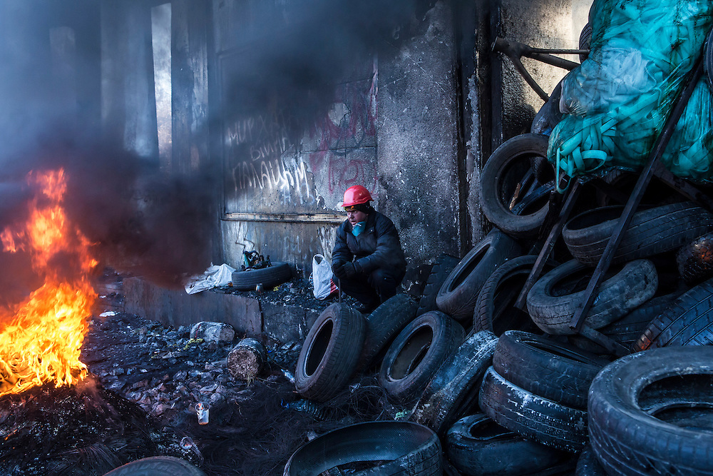 KIEV, UKRAINE - JANUARY 24: An anti-government protester watches tires burn near Dynamo stadium on January 24, 2014 in Kiev, Ukraine. After two months of primarily peaceful anti-government protests in the city center, new laws meant to end the protest movement have sparked violent clashes in recent days. (Photo by Brendan Hoffman/Getty Images) *** Local Caption ***