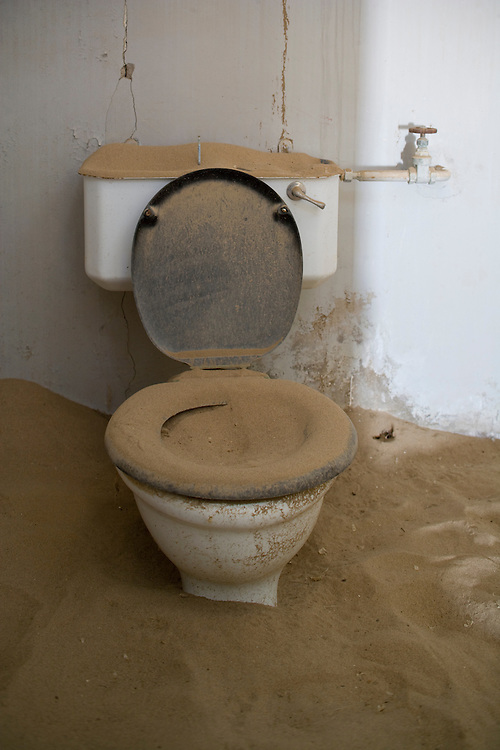 Africa, Namibia, Kolmanskop, Drifting sand fills toilet inside of old building in ghost town of abandoned diamond mining town