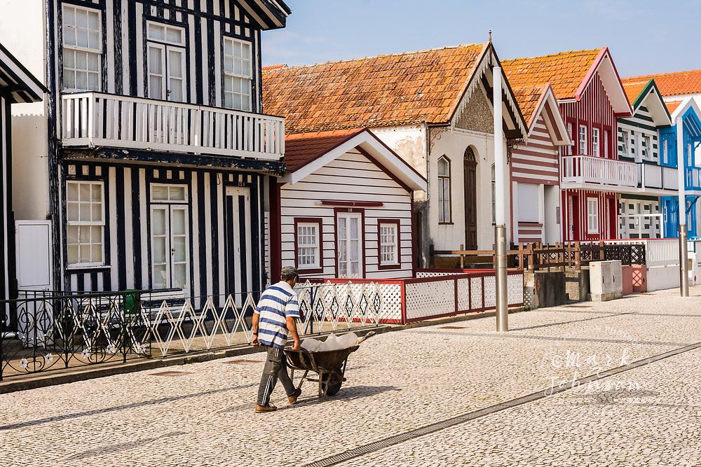 Man in a striped shirt wheeling a wheelbarrow in front of striped buildings, Bairro dos Pescadores, Aveiro, Portugal
