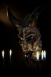 Five black candles and a horned mask.