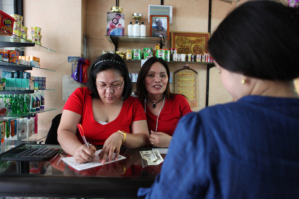 A Filipino shop owner and her assistant prepare paper work for a Filipino domestic worker wanting to send money to her family in the Philippines.