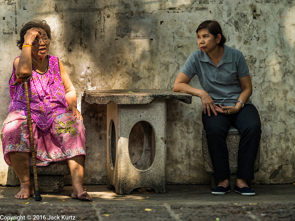 07 APRIL 2016 - BANGKOK, THAILAND: A resident of the squatters' community in Mahakan Fort talks to a Thai Ministry of Health worker assigned to mosquito eradication and avoidance. Mahakan Fort was built in 1783 during the reign of Siamese King Rama I. It was one of 14 fortresses designed to protect Bangkok from foreign invaders, and only of two remaining, the others have been torn down. A community developed in the fort when people started building houses and moving into it during the reign of King Rama V (1868-1910). The land was expropriated by Bangkok city government in 1992, but the people living in the fort refused to move. In 2004 courts ruled against the residents and said the city could take the land. The final eviction notices were posted last week and the residents given until April 30 to move out. After that their homes, some of which are nearly 200 years old, will be destroyed.       PHOTO BY JACK KURTZ