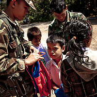 "Thai military at the Thai border examine school children's book bags for drugs or other contraband. Border guards say children of Cambodians living and working in the Thai border town of Klong Yai often pass through the heavily mined ""White Zone"" between the two countries to attend school in Cambodia to maintain their language and culture"