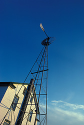Water well powered wind mill outside amish farm house.