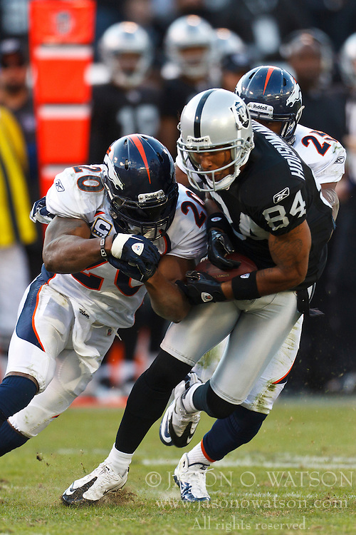 Nov 6, 2011; Oakland, CA, USA; Oakland Raiders wide receiver T.J. Houshmandzadeh (84) catches a pass in front of Denver Broncos strong safety Brian Dawkins (20) during the third period at O.co Coliseum. Denver defeated Oakland 38-24. Mandatory Credit: Jason O. Watson-US PRESSWIRE