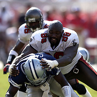 Warren Sapp loses his helmet as he tackles Dallas quarterback Quincy Carter in the 3rd quarter during the game at Raymond James Stadium in Tampa,  Fl. on Sunday (10/26/03) (All names from roster).