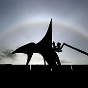 "A worker is silhouetted while working on installation of Alexander Calder's ""Eagle"" at the Seattle Art Museum's Olympic Sculpture Park on Monday, October 2, 2006 as a rainbow-like halo is created by the sun on the high cirrus clouds overhead.  Photo by Joshua Trujillo / Seattle Post-Intelligencer"