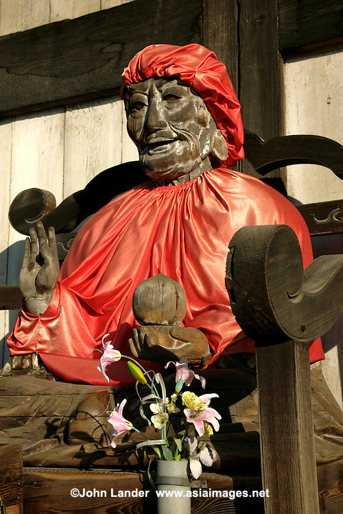 The statue is of Binzuru Yakushi Nyorai or Pindola Bharadvaja, is made of wood,and dates from the Edo period . In Japan,  Binzuru is the most widely revered of the sixteen disciples of Buddha.  He is reported to have excelled in occult powers. In Japan people believe that if you rub a part of the image of Binzuru, and then the corresponding part of your own body, the ailment there will be cured