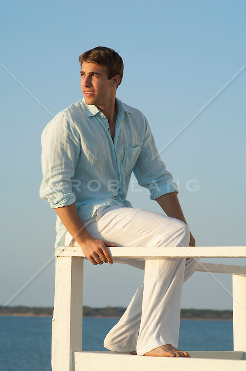 man sitting on a railing by the beach watching the sunset