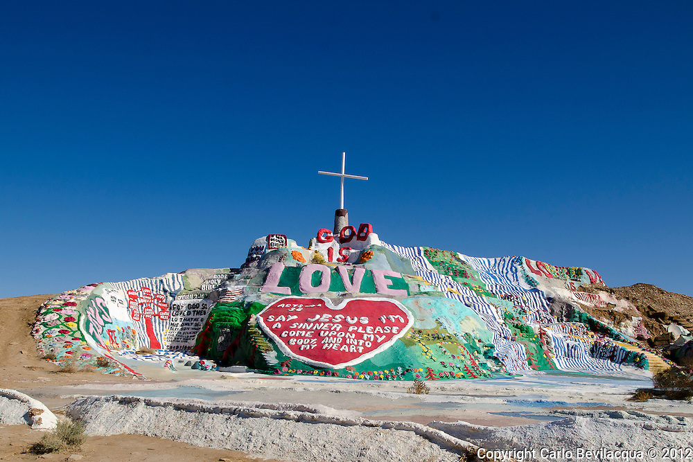 """Salvation Mountain is located in the lower desert of Southern California in Imperial County just east of the Salton Sea and about a hour and a half from Palm Springs. Salvation Mountain is Leonard's tribute to God and his gift to the world with its simple yet powerful message: """"God Is Love."""" Leonard's passion has lovingly created this brilliant """"outsider art """" masterpiece resplendent with not only biblical and religious scripture such as the Lord's Prayer, John 3:16, and the Sinner's Prayer, but also including flowers, trees, waterfalls, suns, bluebirds, and many other fascinating and colorful objects. TheSalvation Mountain is made totally of local adobe clay and donated paint and is truly unique in the United States and probably the world. From its Sea of Galilee at the bottom, to the big red heart in the middle, to the cross at the very top, the reoccurring theme of """"Love"""" is everywhere at Salvation Mountain."""