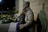 CAMP PENDLETON, CA, JAN 13:  HM2 Herbert Robertson shares a moment withhis wife Janet and son Oliver,7, and Daughter Jovi,5, before deploying to Afghanistan on Monday, January 13, 2014 aboard Camp Pendleton, California. Approximately 140 of the I MEF  command element's 300 Marines and sailors are making a final year long deployment to the Helmand province area of Afghanistan in support of Operation Enduring Freedom.  The marines will join approximately 9000 coalition troops currently in the region and help support Afghan National Security Forces.(Photo by Sandy Huffaker/Getty Images)