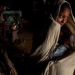 A teenager breast feeds her baby in a rural area outside Bahir Dar, Ethiopia, Aug. 16, 2010. Her husband was maimed shortly after they were married and her lack of education means she must live with her family indefinitely.