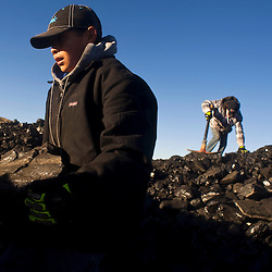 Garrick Israel loads coal with his brother Keanu at the public load out facility of the Kayenta Mine in Black Mesa, Ariz. The two boys were helping their grandparents haul a truckload to heat their home.