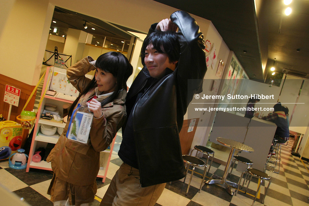 """'MAID CAFE', CUSTOMER POSES FOR PHOTOS WITH WAITRESS. A customer poses for a photo with one of the waitresses in the 'a Home Cafe', a cafe popular with """"Otaku""""- obsesssive type males. Akihabara """"Electric Town"""" district, Tokyo, Japan."""