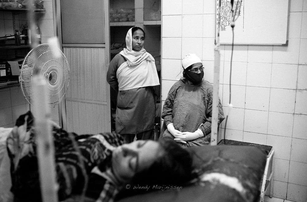 Doctor Musarat and a staff nurse wait for blood during Nafeesa's surgery. The heavy blood loss wasn't controlable and in the end a hysterectomy was needed. With a difficult blood type and lack of donated blood the doctors have to wait to continue the surgery. Lack of resources or in this instance blood make the conditions very difficult for skilled health workers trying to provide care. Karachi, Pakistan, 2010